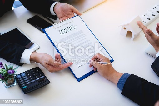 istock lawyer explain the documents contact of insurance of fire and theft a house at office desk. home protection, family, insurance.rent house concept . 1055586262