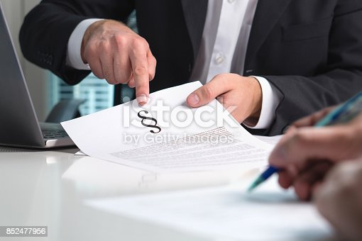 istock Lawyer giving legal advice to a client in office. People in law firm having meeting. Attorney pointing a section sign on paper. 852477956
