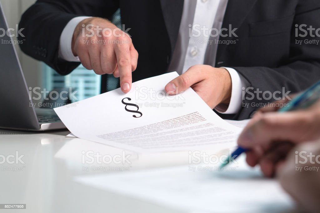 Lawyer giving legal advice to a client in office. People in law firm having meeting. Attorney pointing a section sign on paper. stock photo