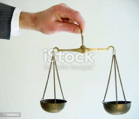 istock Lawyer holding a miniature model of the Scales of Justice 115886692