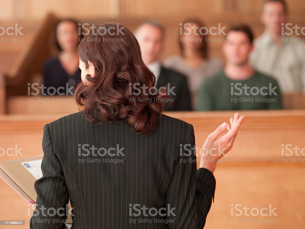Lawyer holding document and speaking to jury in courtroom stock photo