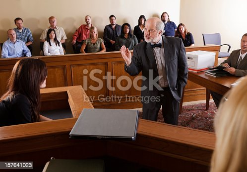 A lawyer questioning a witness in front of the jury in a courtroom.