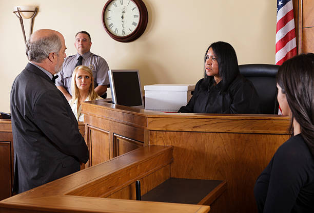 Lawyer in a Courtroom A lawyer talking to the judge in a courtroom. legal trial stock pictures, royalty-free photos & images