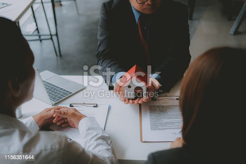 1045876492 istock photo lawyer insurance broker consulting giving legal advice to couple customer about buying renting house. financial advisor with mortgage loan investment contract. realtor selling real estate 1156351644