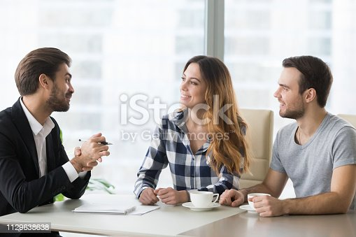 994164754 istock photo Lawyer, insurer or salesman consulting happy millennial couple making offer 1129638638