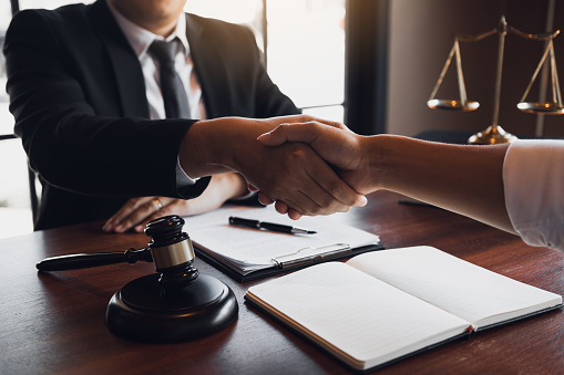 182148217 istock photo Lawyer is currently shaking hands with the client about the success in resolving the case. 1217175175
