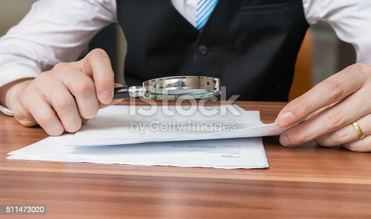 istock Lawyer is inspecting or analysing legal agreement with magnifying glass 511473020