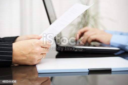 istock Lawyer is reading contract and bussiness client is typing on laptop 465344406