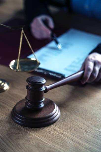 juez abogado leyendo documentos en el escritorio en la sala del tribunal - foto de stock