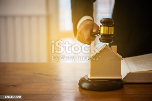 istock lawyer mediating in a property dispute .Auctioneer knocking down a property sale.Real estate sale auction concep. 1186364388