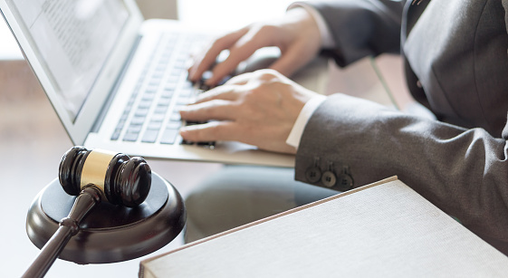 istock Lawyer office. Judge gavel and lawyer working on a laptop. Legal law, advice and justice concept 937930024