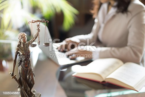 663458084 istock photo Lawyer office. Statue of Justice with scales and lawyer working on a laptop. Legal law, advice and justice concept 1005045882