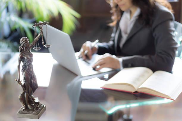 oficina de abogado. estatua de la justicia con escalas y abogados trabajando en un ordenador portátil. concepto legal de la ley, el consejo y la justicia - abogado fotografías e imágenes de stock