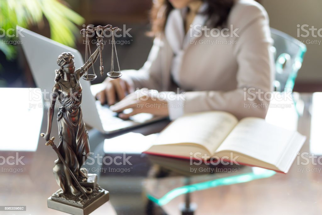 Lawyer office. Statue of Justice with scales and lawyer working on a laptop. Legal law, advice and justice concept - foto stock