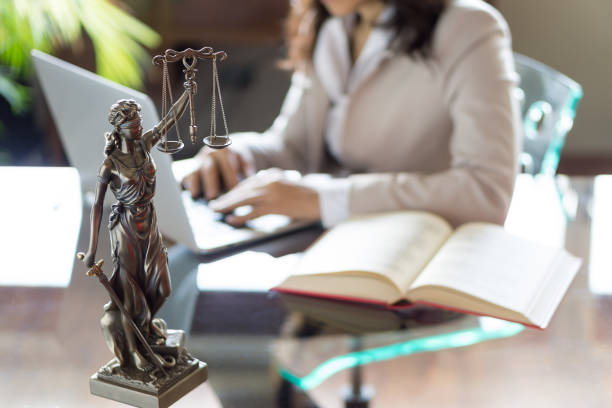 Lawyer office. Statue of Justice with scales and lawyer working on a laptop. Legal law, advice and justice concept stock photo
