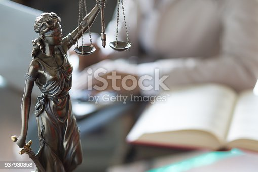 663458084 istock photo Lawyer office. Statue of Justice with scales and lawyer working on a laptop. Legal law, advice and justice concept 937930358