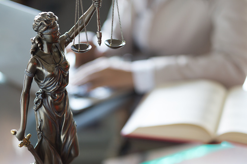 istock Lawyer office. Statue of Justice with scales and lawyer working on a laptop. Legal law, advice and justice concept 937930358