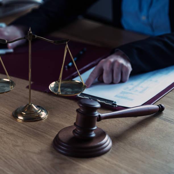Oficina de abogados. Estatua de la Justicia con escalas y abogado trabajando en papeles, consejo y concepto de justicia. - foto de stock
