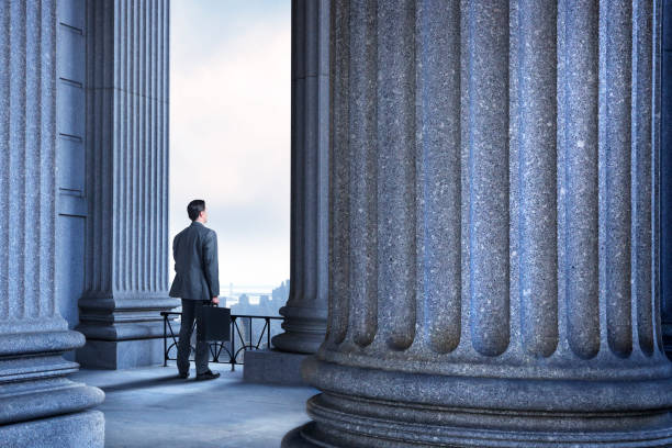 Lawyer Or Businessman Standing In Portico Of Greek Columns stock photo