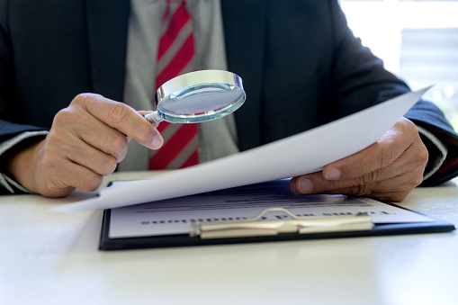 Lawyer or judge use magnifier glass look to the paper for inspection examination to the law case