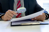 istock Lawyer or judge use magnifier glass look to the paper 1223038258