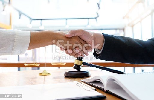 Lawyer or judge  with gavel and balance handshake with client or customer about agreement how to  use arbitration       handshake