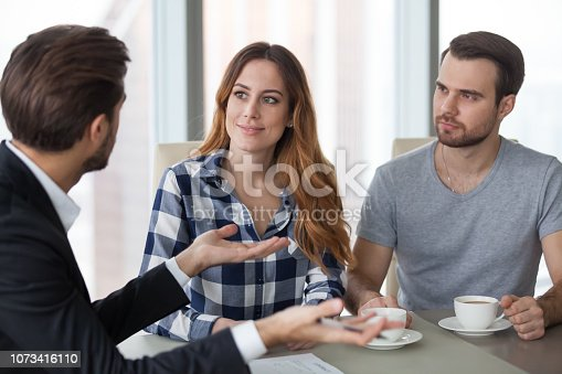963814372istockphoto Lawyer or realtor advisor in suit consulting young couple 1073416110