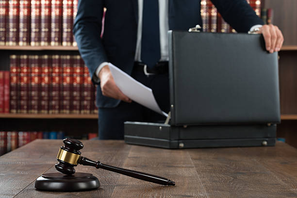 Lawyer Putting Documents In Briefcase Midsection of lawyer putting documents in briefcase with gavel at desk in courtroom legal trial stock pictures, royalty-free photos & images