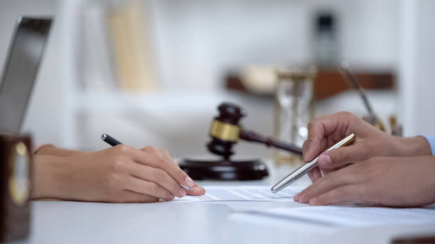Lawyer showing woman where to sign court claim, professional help to plaintiff stock photo