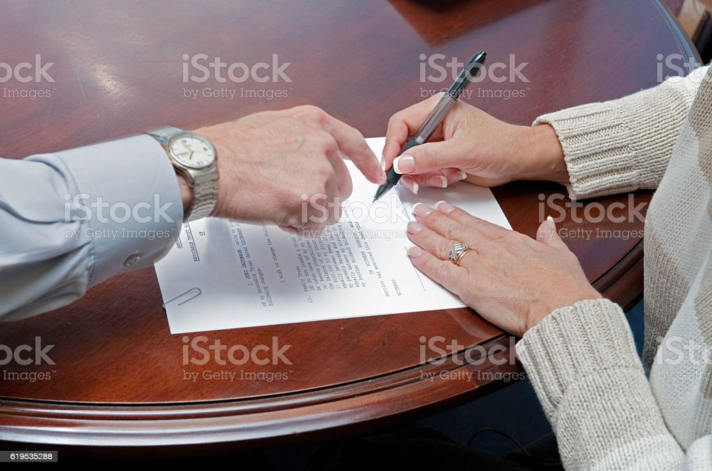Lawyer shows female client where to sign will stock photo