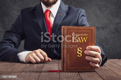 istock Lawyer shows statute book of law in corporations. 1027781632