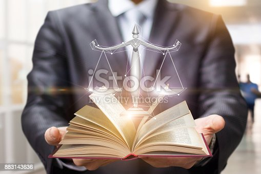 istock Lawyer shows the book and scales of justice . 883143636