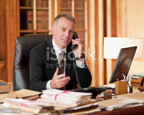 istock Lawyer talking on telephone and gesturing in office 104821115