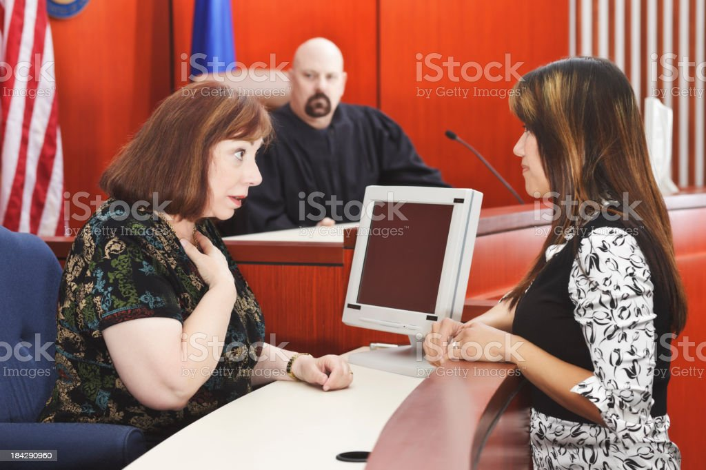 Lawyer Talks to Witness with Judge Seated in Courtroom royalty-free stock photo