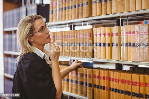 1070981872istockphoto Lawyer wearing glasses and looking for book in the shelf 538203005