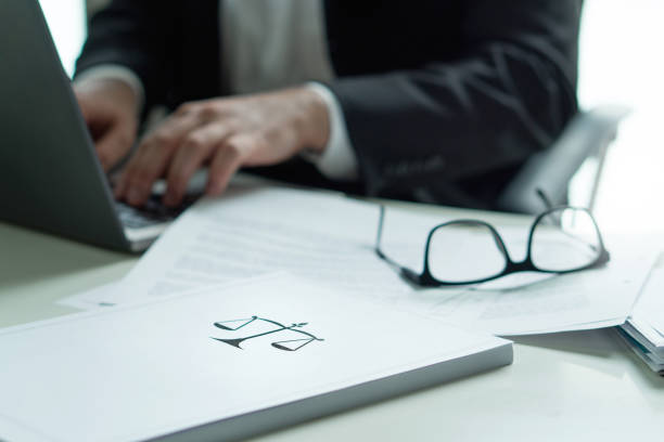 Lawyer working in office. Attorney writing a legal document with laptop computer. Glasses on table. Pile of paper with scale and justice symbol. Law firm and business concept. stock photo