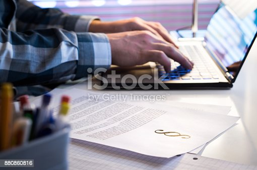 istock Lawyer working in office late at night. Attorney writing a legal document with laptop computer. 880860816
