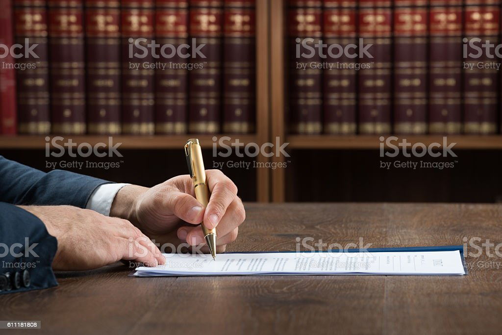 Lawyer Writing On Legal Documents At Desk stock photo