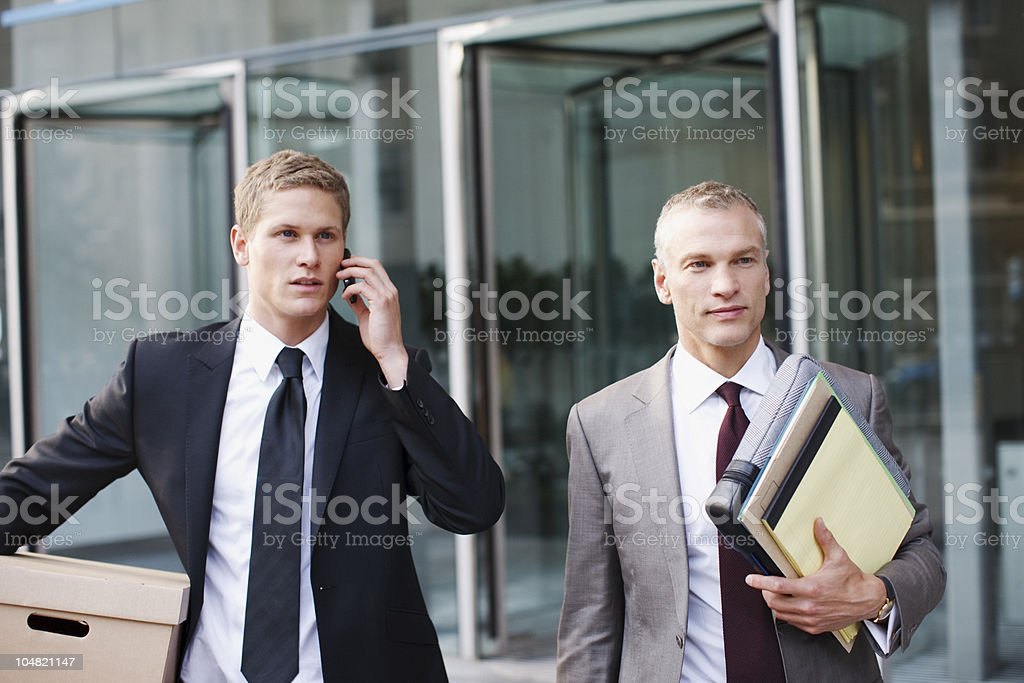 Lawyers carrying files and box outside office building royalty-free stock photo