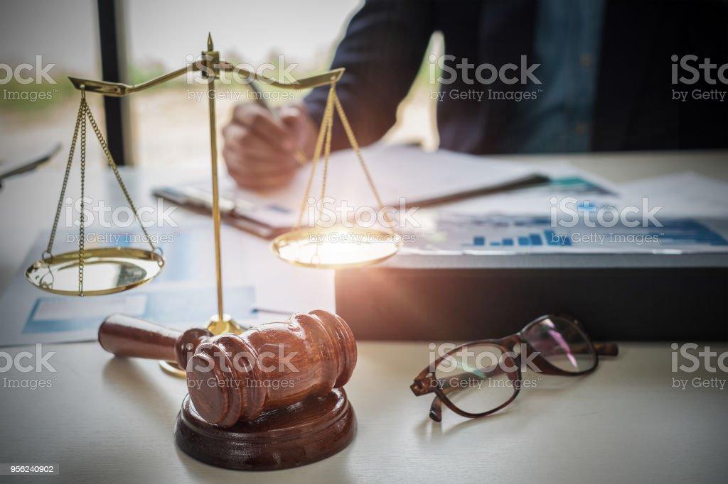 Anwälte, die mit Messing-Skala auf hölzernen Schreibtisch im Büro im Hintergrund. Recht, Rechtsberatung, Beratung, Konzept der Gerechtigkeit. – Foto