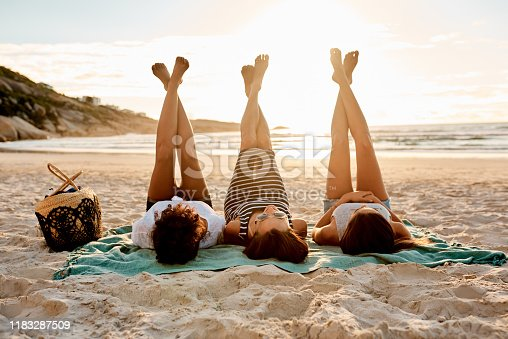 Shot of a group of young women relaxing together with their legs up at the beach