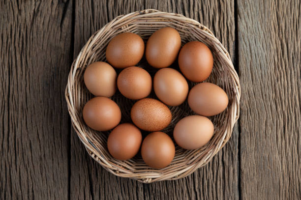 Lay eggs in a wooden basket on a wooden floor. Top view. stock photo