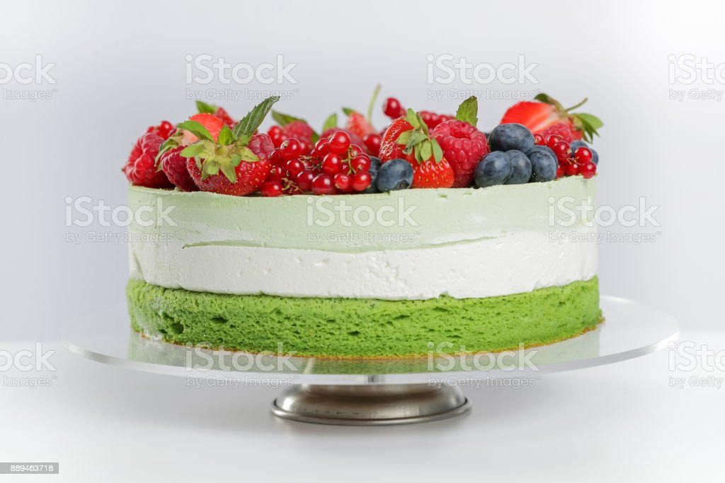 Layer cake with green tea cake and berries stock photo