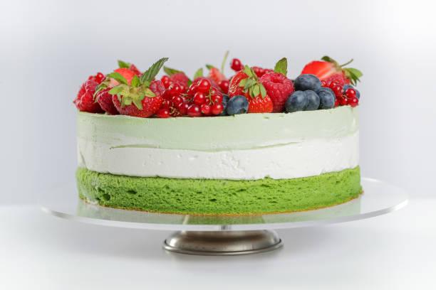schicht-kuchen mit grünem tee kuchen und beeren - biskuitboden stock-fotos und bilder