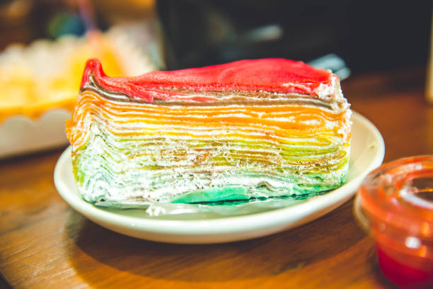 schicht käsekuchen bunte regenbogen süße dessert mit tauchbeschichtung oben - regenbogen käsekuchen stock-fotos und bilder
