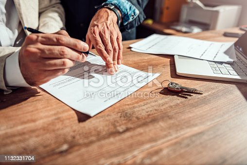 1072035844istockphoto Layer pointing at contract 1132331704
