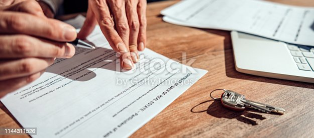 1072035844istockphoto Layer pointing at contract 1144311526