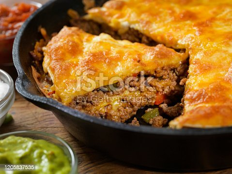 Layered, Beef Taco Pie Baked in a Cast Iron Skillet with Sour Cream, Salsa and Guacamole