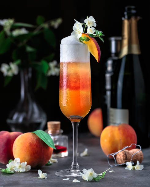 Layered bellini cocktail with peaches on dark background stock photo