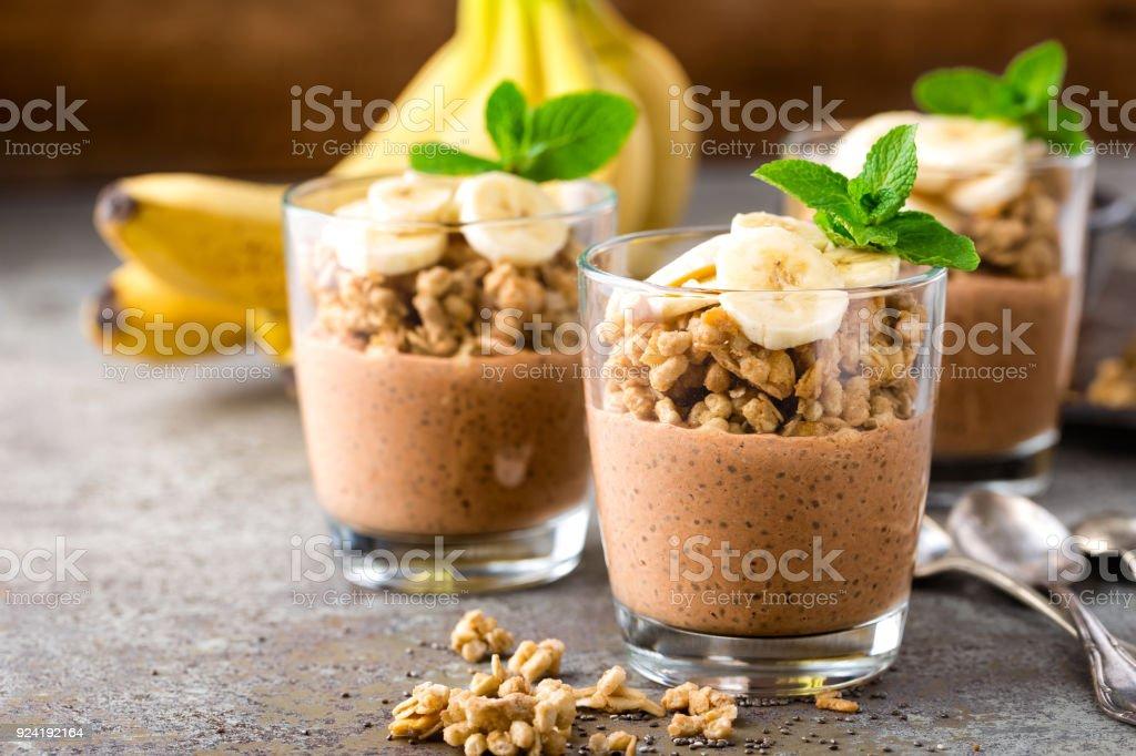 Layered chocolate chia pudding parfait with banana, granola and yogurt, dessert stock photo
